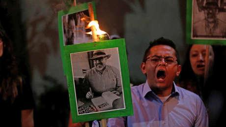 Periodistas y manifestantes sostienen fotografías del periodista Javier Valdez, durante una protesta para exigir justicia en los asesinatos de periodistas, en mayo de 2017.
