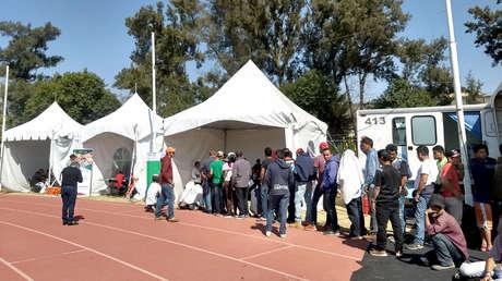 Migrantes aguardan en una fila para recibir atención médica en las carpas habilitadas para dicho fin.