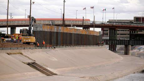 Trabajadores y oficiales de la patrulla fronteriza de los EE. UU. están parados junto a una excavadora de la nueva valla en El Paso, Texas, el 5 de febrero. 2019.