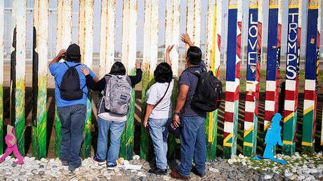 Una familia mexicana ante el muro fronterizo entre EE.UU. y México, en la ciudad mexicana de Tijuana, el 23 de diciembre de 2018.