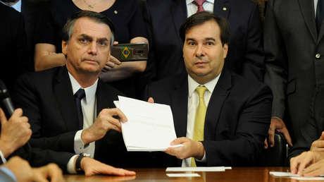 El mandatario de Brasil, Jair Bolsonaro, y el presidente del Congreso, Rodrigo Maia, posan con el proyecto de reforma de pensiones, Brasilia, 20 de febrero de 2019.