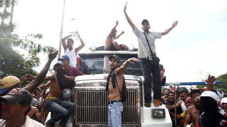 """Manifestantes dirigen gestos de desaprobación a la Policía de Venezuela desde un camión con """"ayuda humanitaria"""" en Cúcuta (Colombia), el 23 de febrero de 2019."""