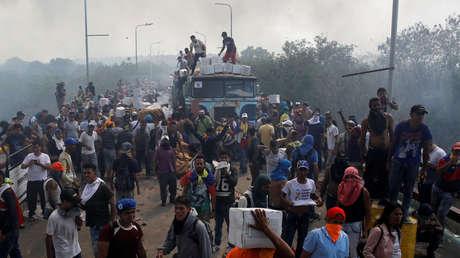 Opositores descargan la 'ayuda humanitaria' tras el incendio en uno de los camiones, Cúcuta, Colombia, 23 de febrero de 2019.