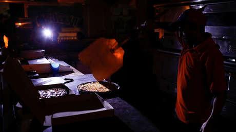 Un hombre cocina a la luz de las velas y linternas en una pizzería en Caracas, el 9 de marzo de 2019.