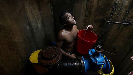 Los lugareños recolectan agua de un ducto de agua subterránea en Caracas, Venezuela, 12 de marzo de 2019.
