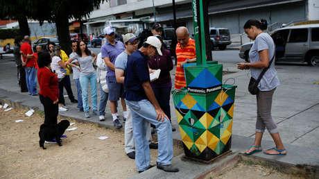 Gente haciendo cola para cargar sus teléfono en un panel solar en una calle de Caracas, Venezuela, 10 de marzo de 2019.