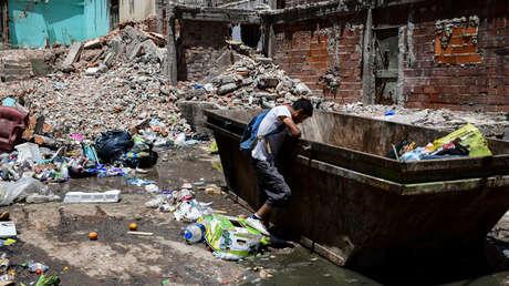 Un hombre busca ropa y comida en un contenedor de basura en la Villa 20 de la Ciudad de Buenos Aires, el 11 de enero del 2019.