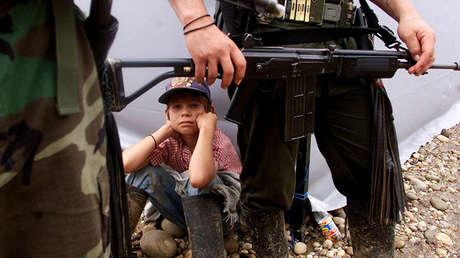 Un niño colombiano junto a dos rebeldes de las Fuerzas Armadas Revolucionarias de Colombia (FARC), en Villa Colombia, el 29 de abril de 2000.