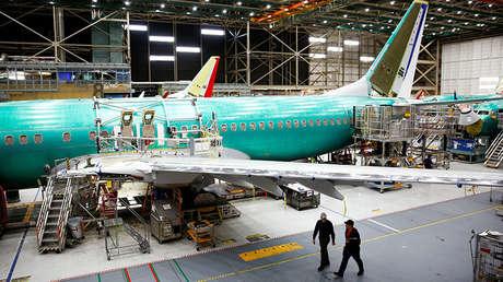 Trabajadores bajo un avión 737 Max en la fábrica de Boeing en Renton, EE. UU., 27 de marzo de 2019.