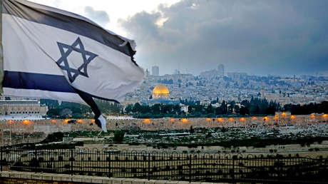 Bandera israelí en el Monte de los Olivos con la mezquita de fondo, Jerusalén, 27 de marzo de 2019.