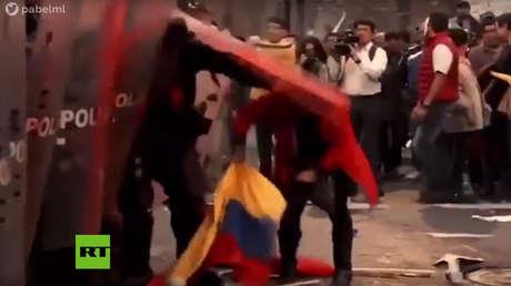 Un miembro de la Policía Nacional de Ecuador golpea a patadas a una mujer, el 16 de abril del 2019, en Quito.