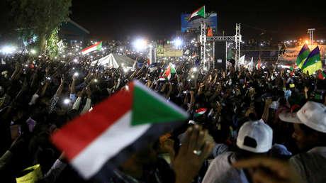 Manifestantes ondean banderas nacionales durante una protesta antigubernamental frente al ministerio de Defensa de Sudán, en Jartum, el 21 de abril de 2019.