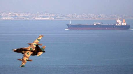 Un avión de combate iraní vuela cerca de un tanque de petróleo durante unas maniobras navales en el golfo de Omán, 5 de abril de 2006
