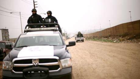 La Policía y los soldados cruzan la valla fronteriza entre México y los EE. UU, en Tijuana, el 13 de marzo del 2018.