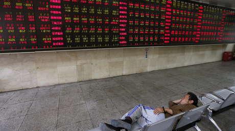 Un hombre echa una siesta en una oficina de corretaje, Pekín, China.