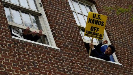 Un hombre sostiene un letrero en la ventana de la embajada venezolana en Washington. 1 de mayo de 2019.