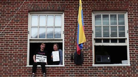 Activistas muestran carteles desde una de las ventanas de la Embajada de Venezuela en Washington, 25 de abril de 2019.
