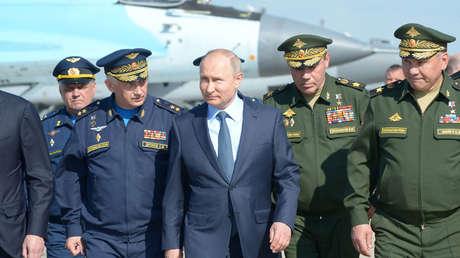 El presidente ruso Vladímir Putin (centro) al lado del ministro de Defensa, Serguéi Shoigú (derecha) y el jefe del Estado Mayor General, Valeri Guerásimov (segundo a la derecha) en el centro de pruebas en Ajtúbinsk.