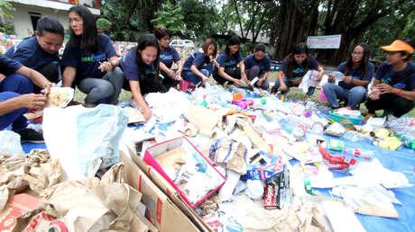 Activistas manejan basura en Ciudad Quezón (Filipinas).