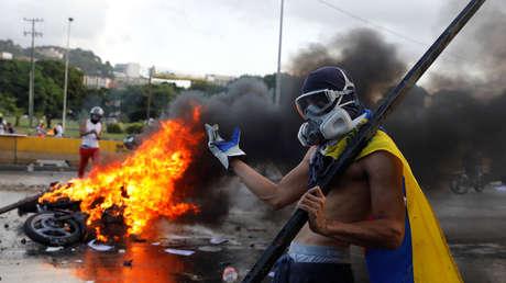 Un encapuchado hace un gesto en una 'guarimba' en Caracas, Venezuela. 22 de junio de 2017.
