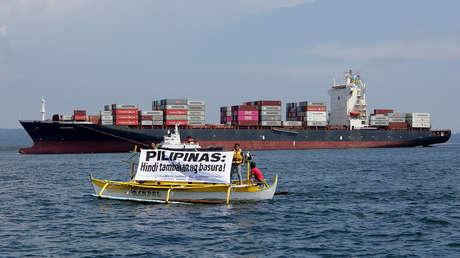 Activistas de Greenpeace extienden una pancarta frente al barco con 69 contenedores en Manila, Filipinas. 30 de mayo de 2019.
