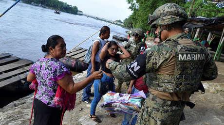 Policía mexicano solicita una identificación a una mujer de Guatemala tras cruzar el Río Suchiate, México, 16 de junio de 2019.