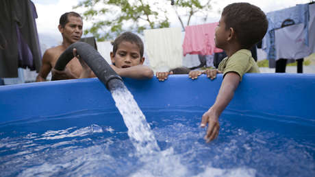 Niños llenan un tanque de agua en un vecindario en Caracas, Venezuela. 7 de noviembre de 2009.
