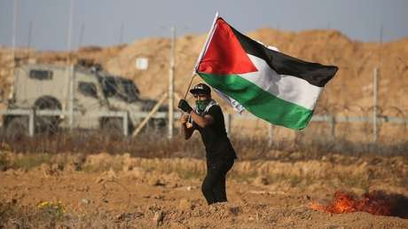 Un manifestante ondea una bandera palestina cerca de la frontera entre Israel y Gaza.