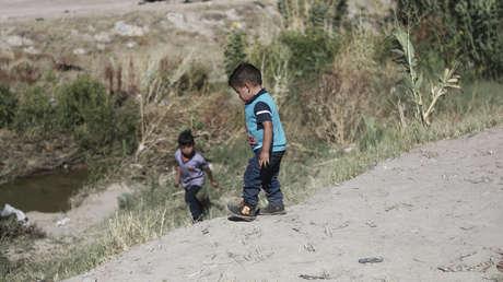Niños migrantes esperan a su padre en la parte mexicana del Río Bravo antes de cruzar hacia EE.UU. para rendirse ante las autoridades estadounidenses, el 15 de junio de 2019.