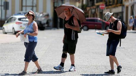 Turistas con un paraguas para protegerse del sol durante la ola de calor. Ronda, España, 26 de junio de 2019.