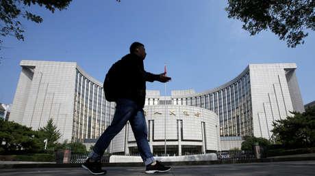 Un hombre pasa frente a la sede del Banco Popular de China, Pekín.