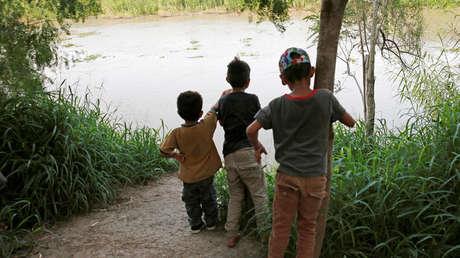 Niños migrantes centroamericanos miran el Río Bravo en Matamoros, Tamaulipas, México, 27 de junio de 2019.