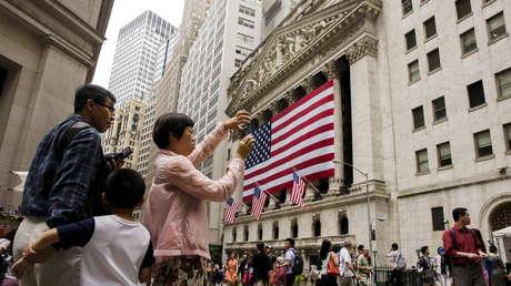 Turistas chinos toman fotos frente a la Bolsa de Nueva York.