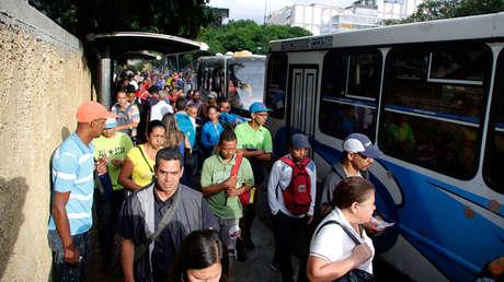 Gente en una fila para tomar el autobús en Caracas, Venezuela, martes 23 de julio de 2019.