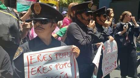 Mujeres disfrazadas de policías protestan para exigir justicia en el caso de una joven que habría sido violada por cuatro agentes cuando regresaba de una fiesta.