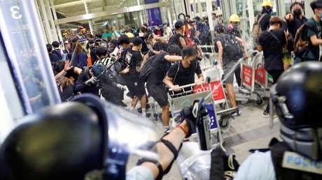 La Policía usa gas pimiento durante choques con manifestantes en el aeropuerto internacional de Hong Kong, China, el 13 de agosto de 2019.