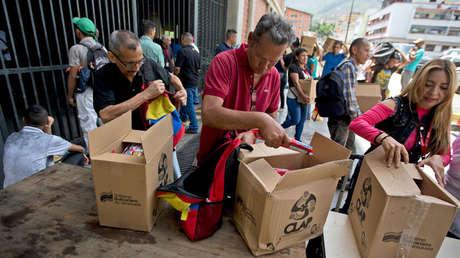 Personas con sus cajas del  Comité Local de Abastecimiento y Producción (CLAP) en Caracas, Venezuela, el 6 de julio de 2018.