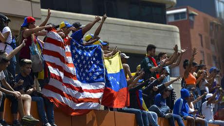 Manifestantes sostienen la bandera de EE.UU. junto a otra venezolana en Caracas, Venezuela, el 1 de mayo de 2019.
