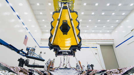 Ingenieros ponen el telescopio Webb en posición momentos antes del ensamblaje.