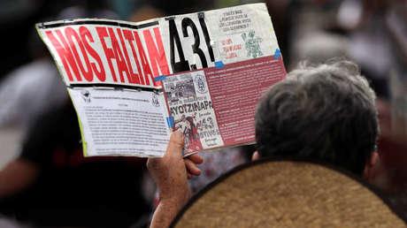 Una mujer sostiene un cartel para conmemorar el mes 55 de la desaparición de los normalistas de Ayotzinapa. Ciudad de México, México, 26 de abril de 2019