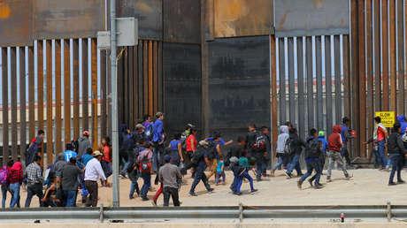 Migrantes centroamericanos caminan mientras son detenidos por agentes de la Patrulla Fronteriza de EE.UU. en el muro fronterizo en Ciudad Juárez, en el estado mexicano de Chihuahua, el 7 de mayo de 2019.