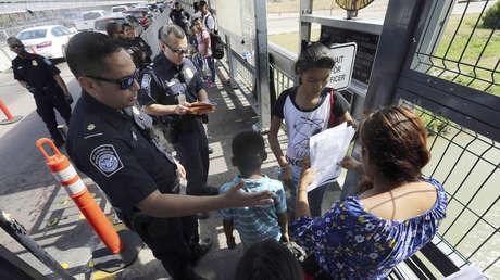 Agentes fronterizos de EE.UU. verifican documentos de solicitantes de asilo en el Puente Internacional 1 en Nuevo Laredo, México, el 17 de julio de 2019.
