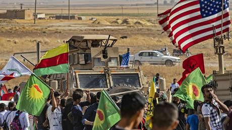 Kurdos cerca de un vehículo militar de EE.UU. durante una manifestación en la ciudad de Ras al-Ayn, Siria, el 6 de octubre de 2019