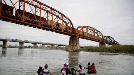 Migrantes de El Salvador cruzan el río Bravo hacia los EE.UU, en Piedras Negras, México