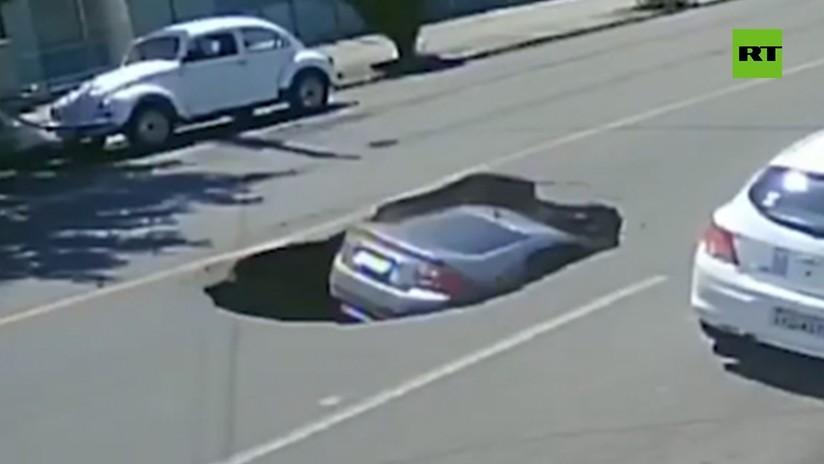 VIDEO: Un coche cae en un socavón que un camión abre tras su paso por una vía de Brasil
