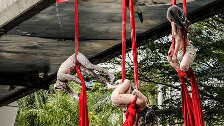 'Un país que siembra cuerpos': Artistas desnudos y colgados de un puente denuncian los asesinatos en Colombia