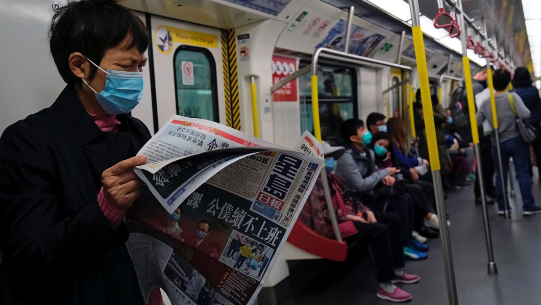 Un pasajero lame sus dedos y se limpia en un pasamanos del metro de Hong Kong en medio de la crisis por el coronavirus (VIDEO)