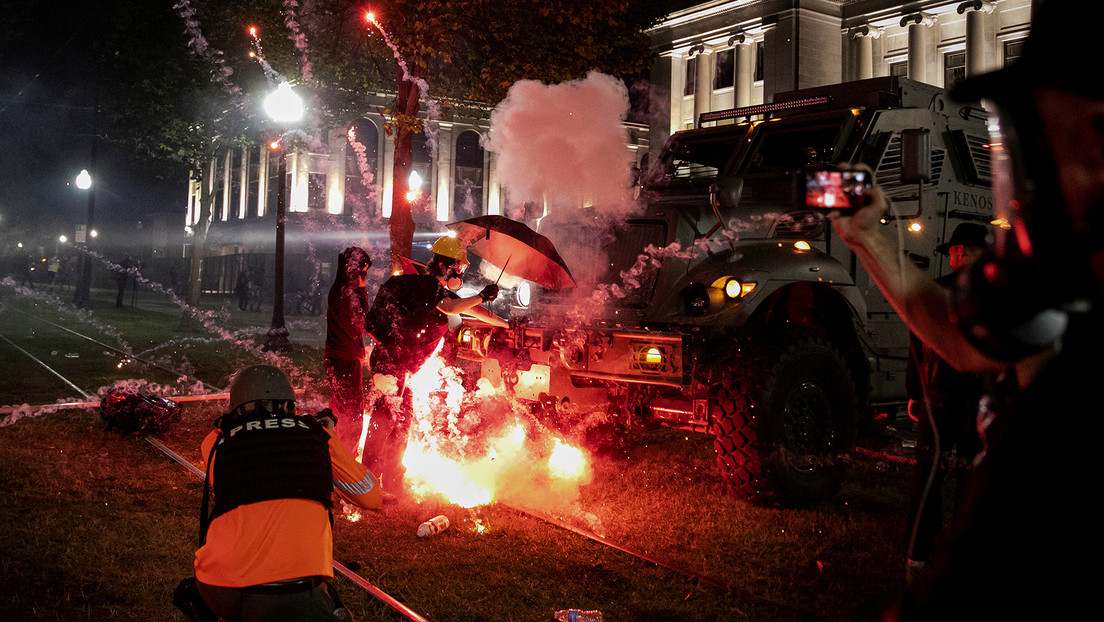 An incendiary device goes off in front of a Kenosha Country Sheriff Vehicle as demonstrators take part in a protest following the police shooting of Jacob Blake, a Black man, in Kenosha