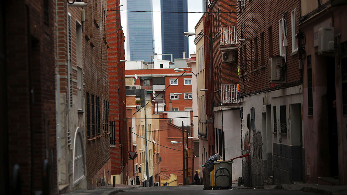 A man searches for food in a garbage container along a street, against the backdrop of the Four Towers business district pictured, in Tetuan