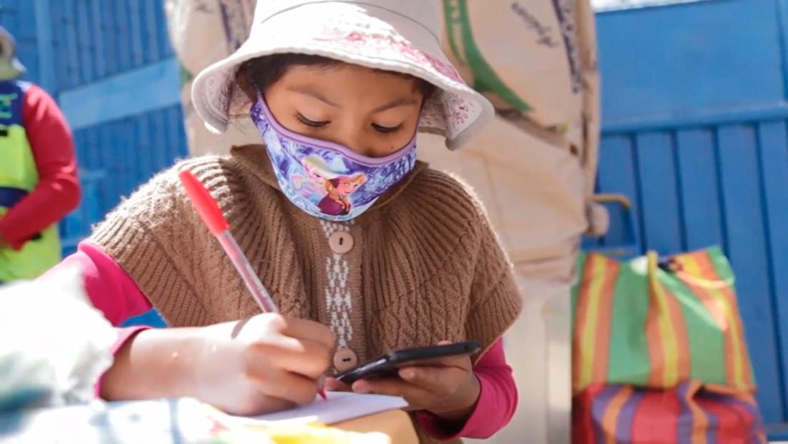 Niña peruana de 10 años estudia a través de un celular, mientras ayuda a su tía en un puesto de venta de refrescos